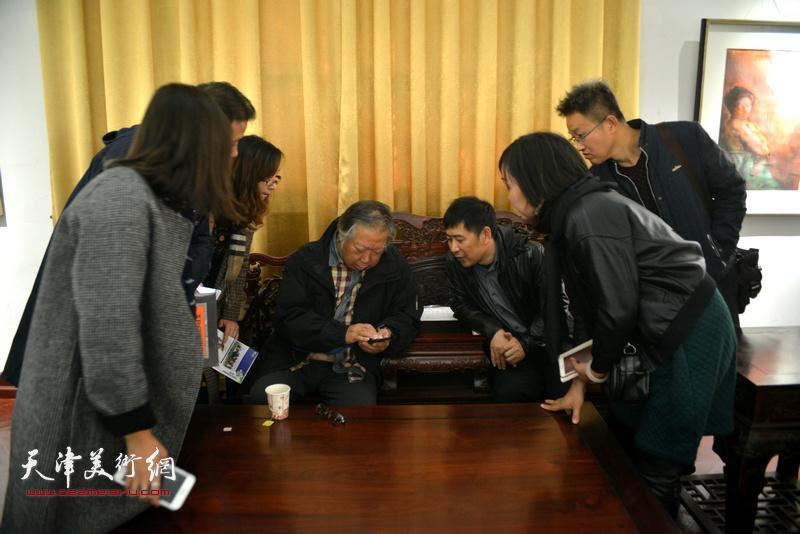 石增琇与谢红等观赏手机上拍摄的作品。