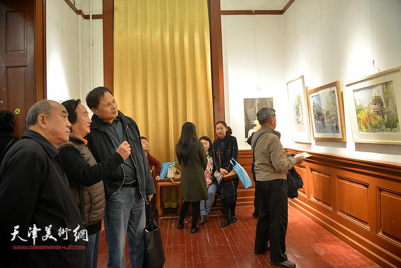 陈重武与乔雨林等观赏展出的作品。