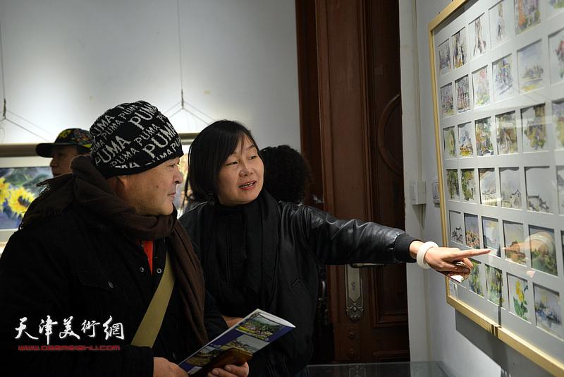 蒋长虹与谢红观赏展出的作品。