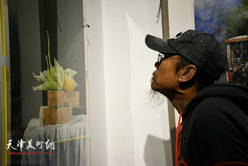 王岩明观赏展出的作品。