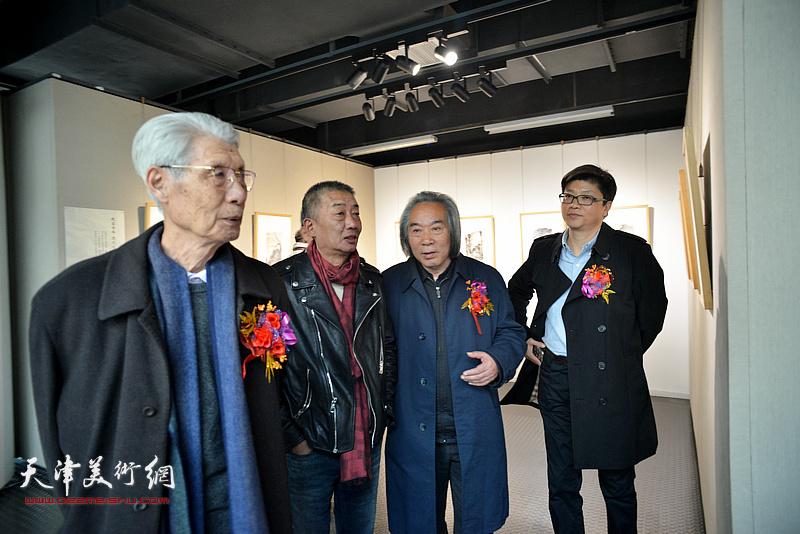 李旭飞陪同邓国源、杨德树、霍春阳观赏展出的作品。