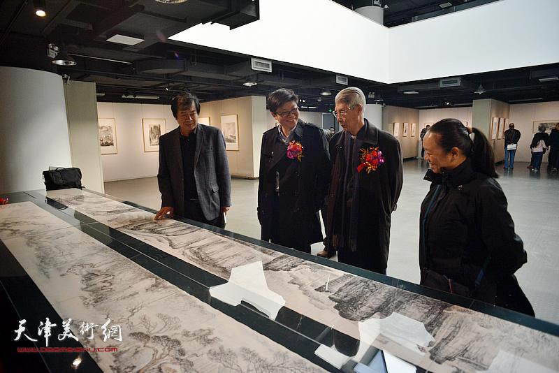 李旭飞陪同杨德树、史振岭观赏展出的作品。