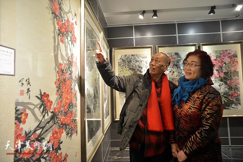张学强、王俊英在画展现场观看画作。