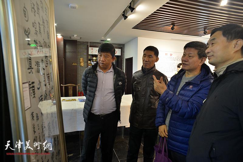 李向群与来宾在画展现场观看展品。