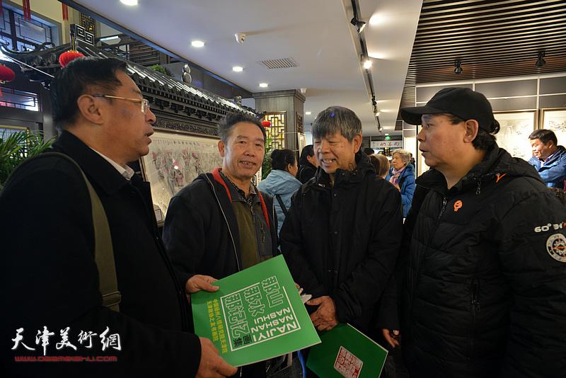 郭凤祥、赵俊山、张礼军、温洪琪在画展现场交谈。