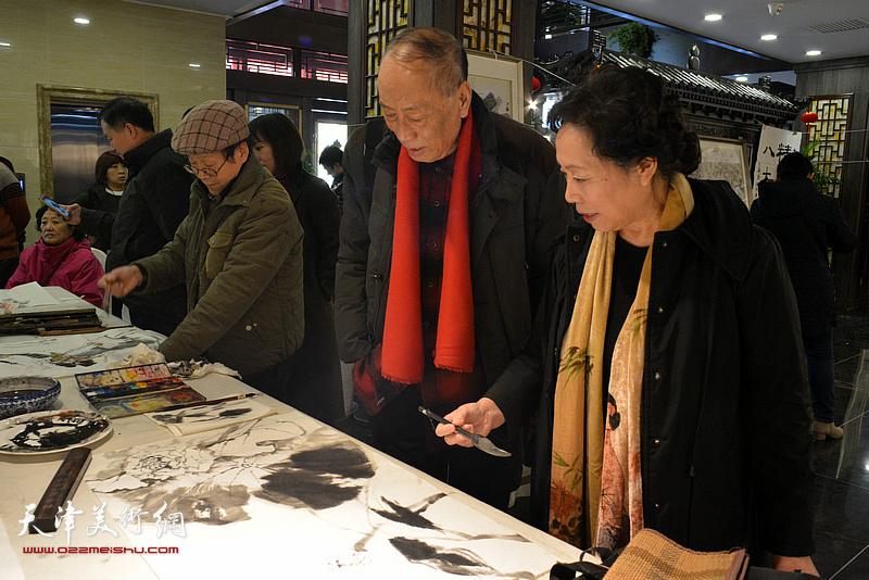 张学强、崔燕萍在画展现场挥毫创作。