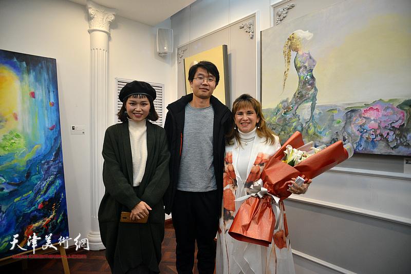 天津美术学院教师王盟、油画系研究生王莫愁向那文丽女士献花。