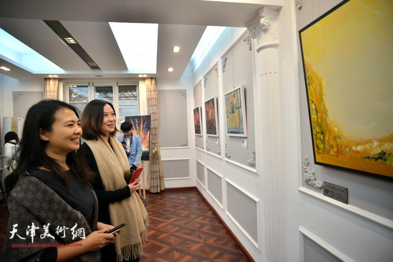 策展人于芷若与来宾观赏展出的画作。