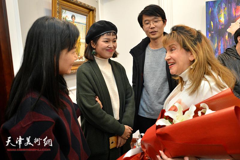 那文丽女士与来宾在画展现场交流。