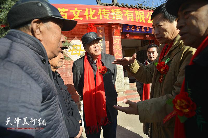 邵佩英、李桂金、谢天强、陈之海在揭牌现场与村民交谈。