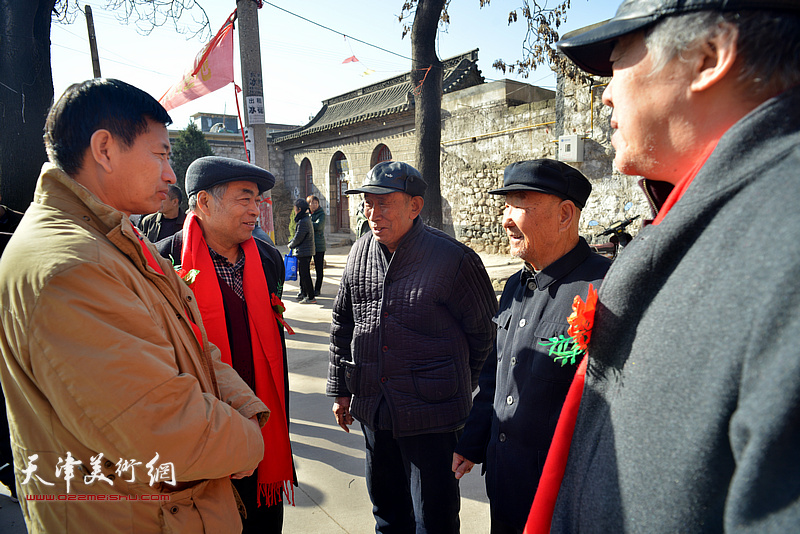 李桂金、谢天强在揭牌现场与村民交谈。