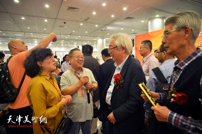 杨德树、王美芳、赵国经与欧豪年在画展现场交谈。