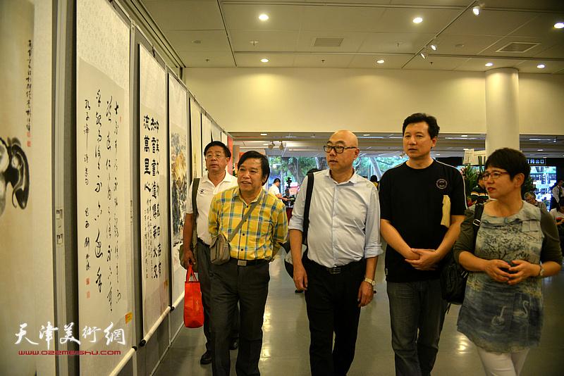 李耀春、赵俊山、高博、张福有、车凤云在观赏展出的作品。
