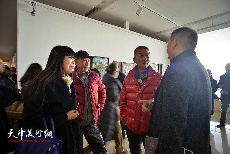 邓国源与来宾在画展现场交流。