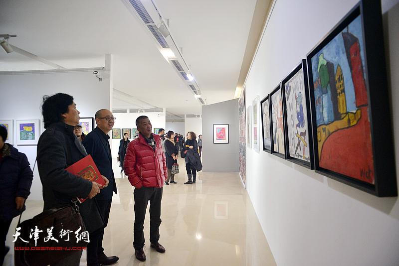 邓国源、王琨、马驰在观赏展出的画作。
