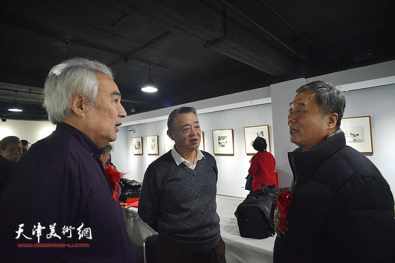 马明、邢立宏、王毓民在画展现场交流。