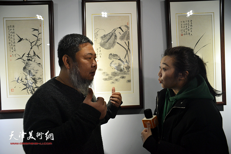 张法东在画展现场接受媒体的采访。