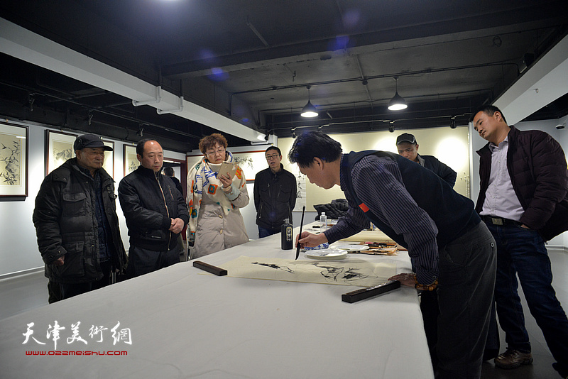 李宝志在画展现场作画。