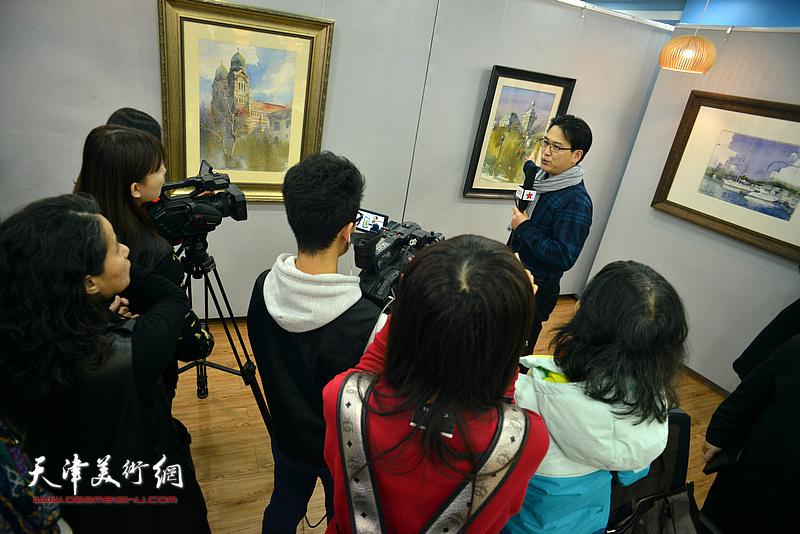 滑寒冰向到场媒体与观众介绍展出的作品。