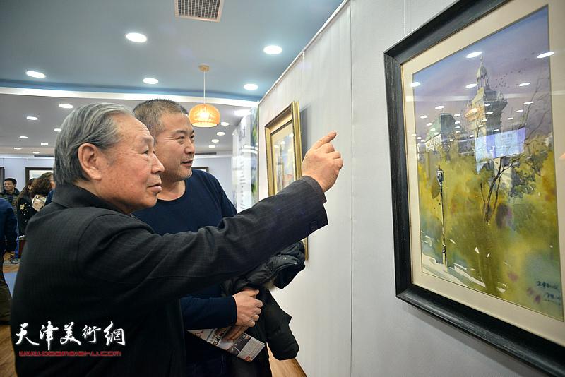 李宗儒、李金玺在观赏展出的水彩作品。