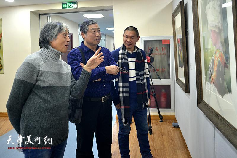 胡万荣、孟东生、郑伟在观赏展出的水彩作品。