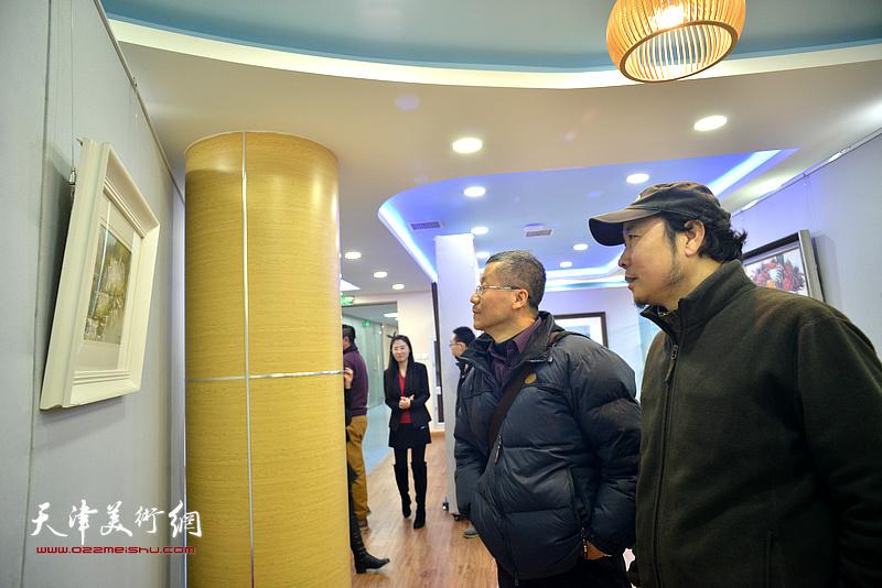 吕培桓、杨俊甫在观赏展出的水彩作品。