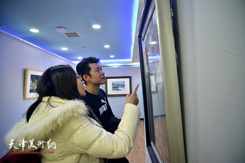 李垚在观赏展出的水彩作品。