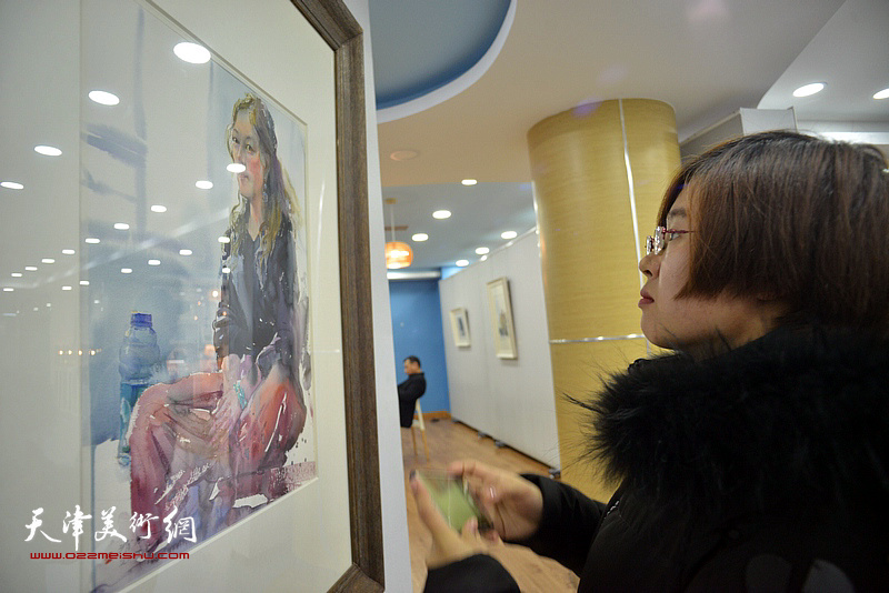 孔滋在观赏展出的水彩作品。