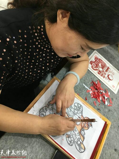 """刘长会在现场创作剪纸""""福""""字。"""