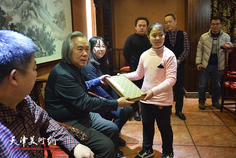 李思瑶向师傅霍春阳赠送文房四宝。
