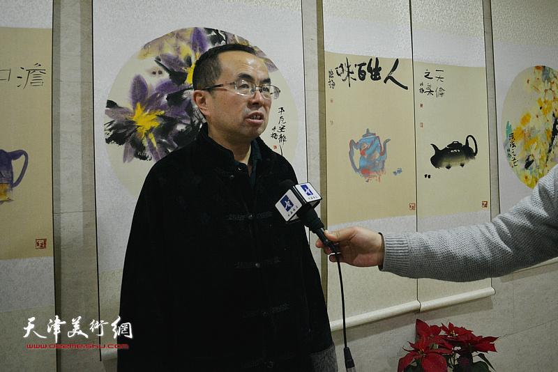 吴川淮在画展现场接受媒体采访。