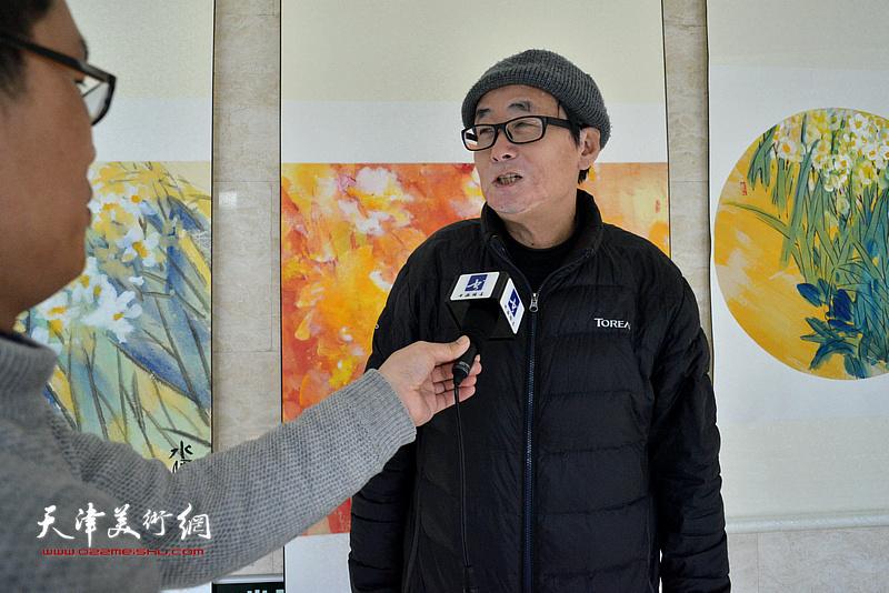 丛培军在画展现场接受媒体采访。