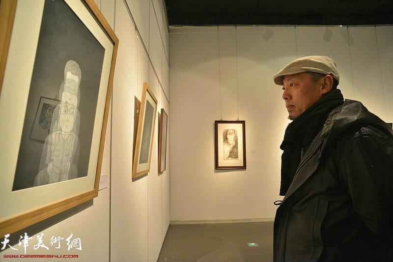 谭勋在画展上观赏展出的作品。