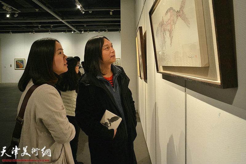 郝青松在画展上观赏展出的作品。