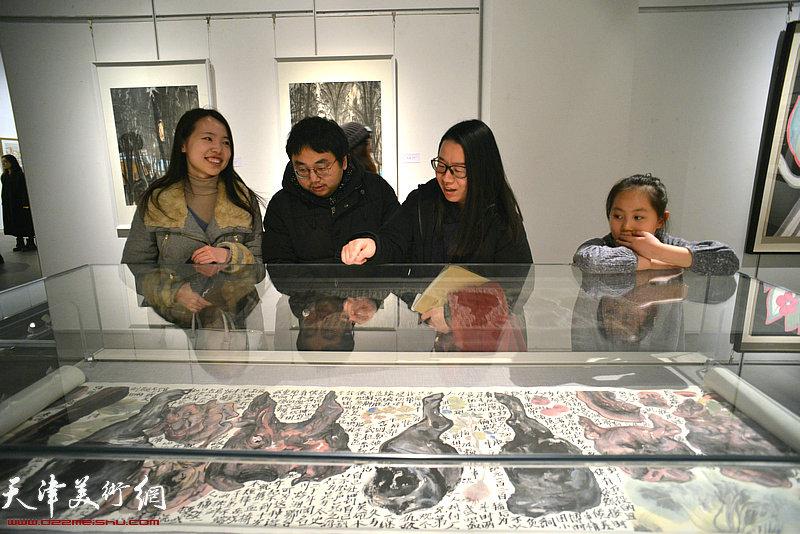张坤在画展上观赏展出的作品。