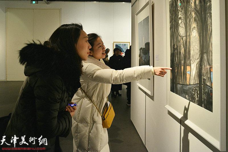 胡月在画展上观赏展出的作品。