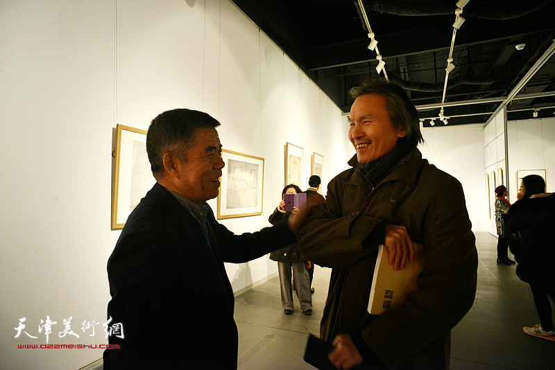 杨维民与郭雅希在画展上交谈。
