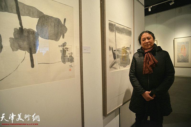 郑岱在展出的画作前。