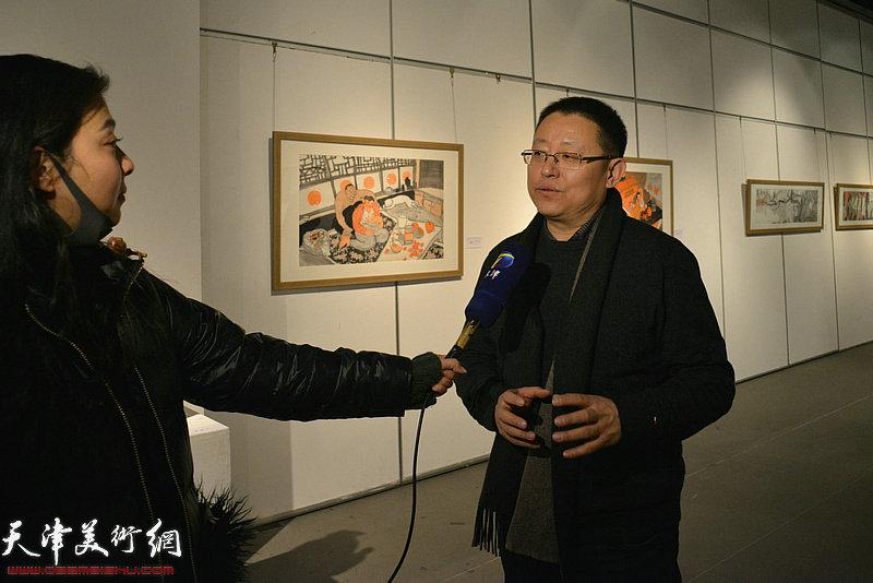 参展画家李晶彬在画展现场接受媒体采访。