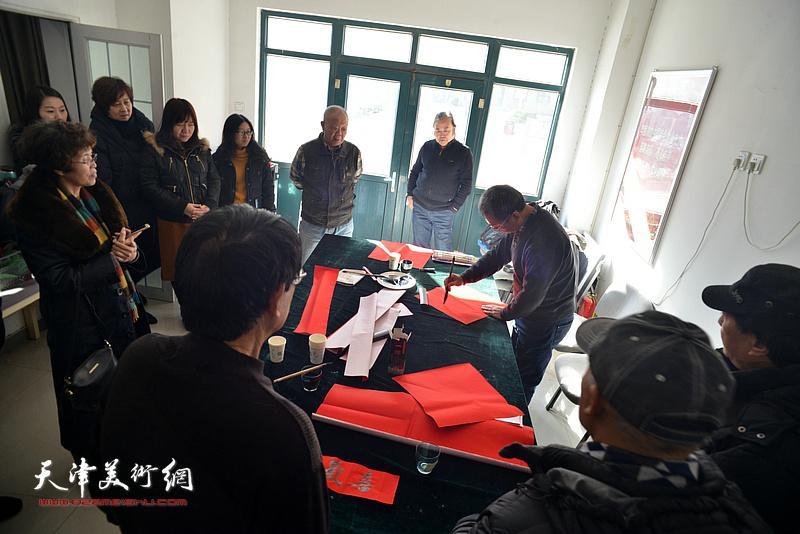 洪喆文化书画院书画家在社区写福字。