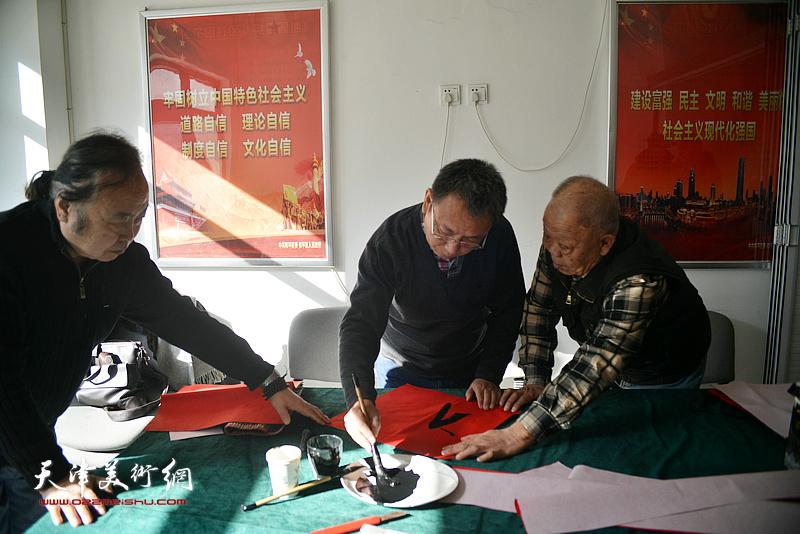 洪喆文化书画院书画家周志军、李金恒、谢纯灏在社区写福字。