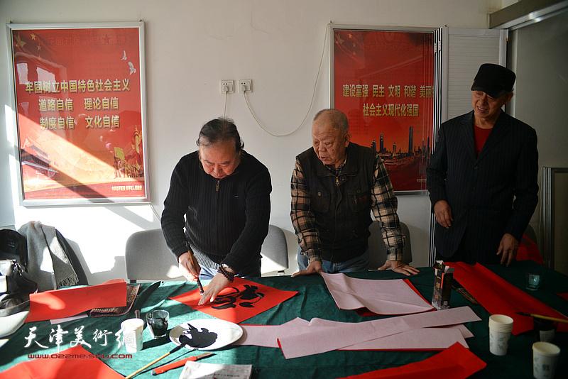 洪喆文化书画院书画家李新明、周志军、谢纯灏在社区写福字。