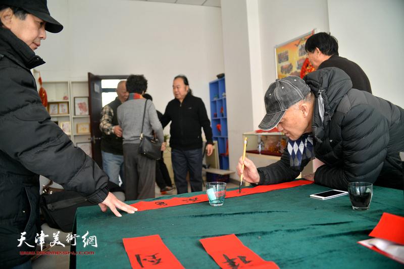 洪喆文化书画院书画家冯士刚、马永庆在社区写福字。
