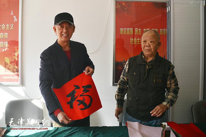 左起:洪喆文化书画院书画家李新明、谢纯灏在活动现场。