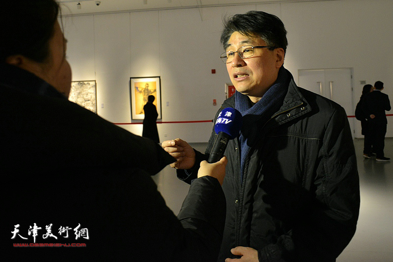 天津美术学院副院长郭振山在画展现场接受媒体采访。