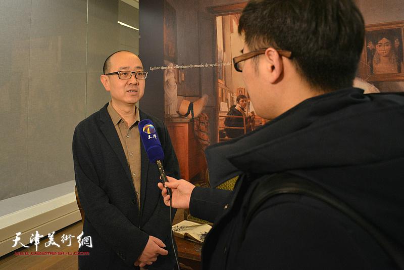 天津美术馆馆长马驰在展览现场接受媒体采访。