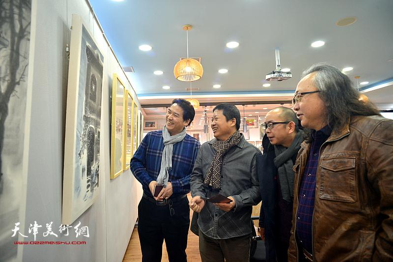 魏瑞江与朱志刚、滑寒冰、阚传好观赏展出的画作。