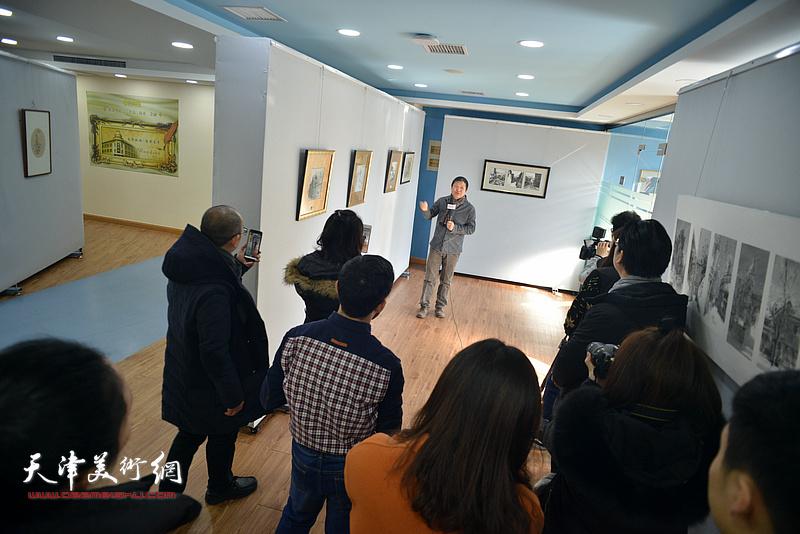 魏瑞江向媒体、观众介绍展出的画作。