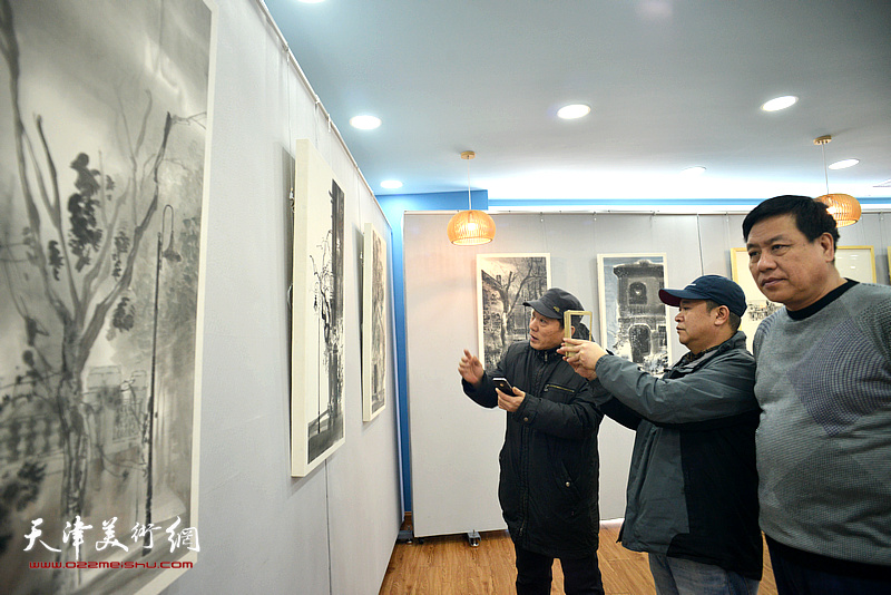 高原春、段博君、宋世凯观赏展出的画作。