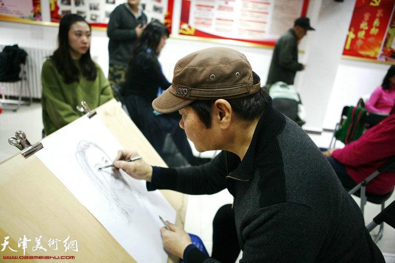 画家叶祖茂为社区居民画肖像。